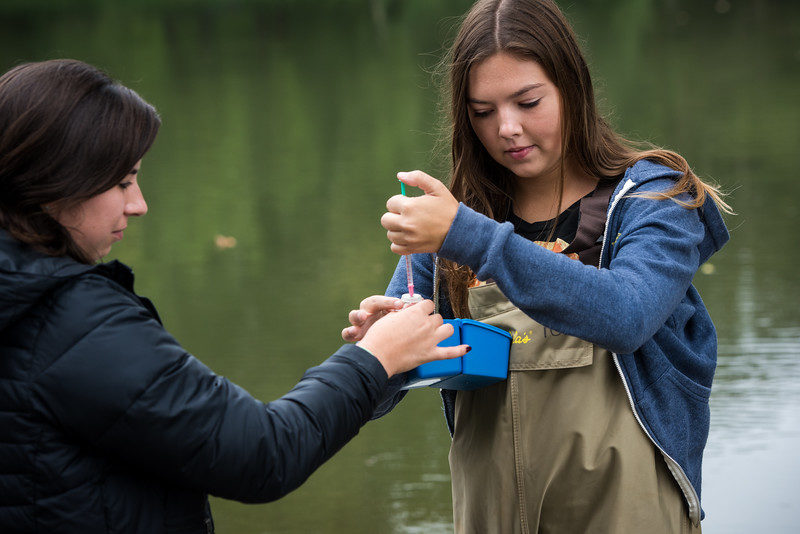 Two young women collect water samples with pipettes by a river