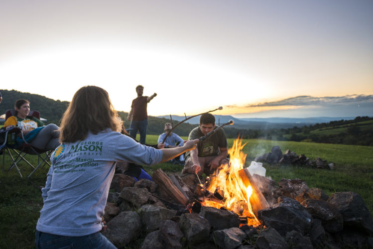 Students roast marshmallows at campfire with mountain view in background