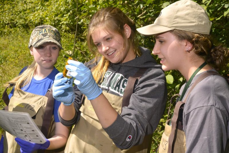 Three young women inspect bottle with water sample from nearby creek