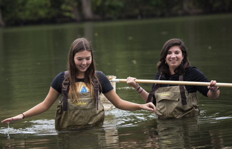 Two young women stand waist-deep in a watershed collecting samples